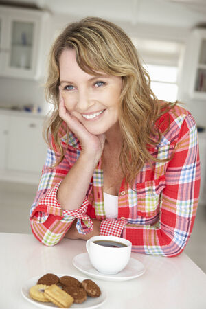 mid age: Mid age woman with coffee and biscuits at home