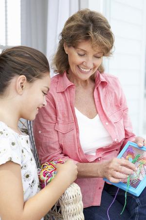 punto croce: Senior donna facendo punto croce con la nipote Archivio Fotografico
