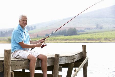 Superior hombre pesca en el embarcadero Foto de archivo - 33553151