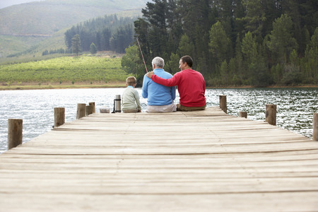 a year older: Father,son and grandfather fishing Stock Photo