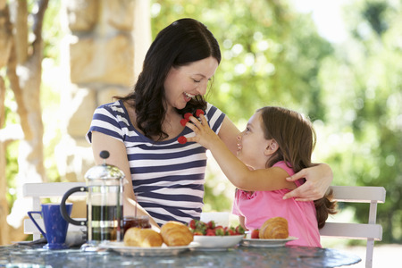 Mother and daughter eating breakfast outdoors photo
