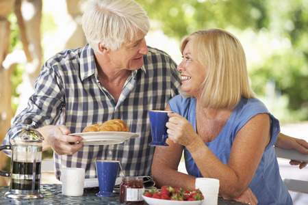 Senior couple eating breakfast outdoors Stockfoto