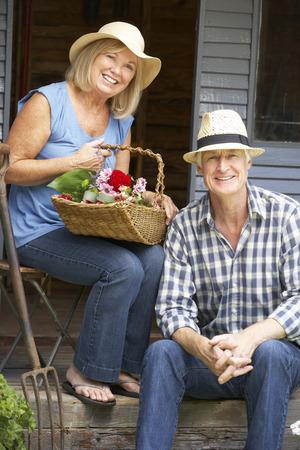 Senior couple sitting on veranda with flowers photo