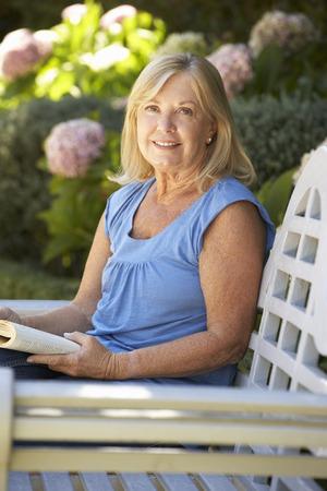 Senior woman reading in garden photo