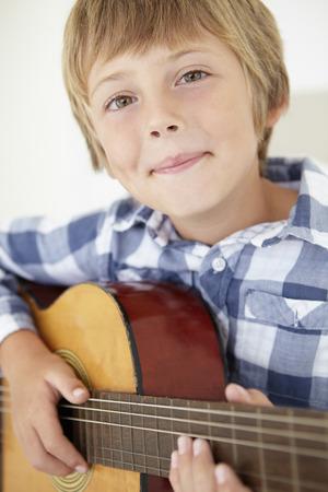 Jonge jongen spelen akoestische gitaar Stockfoto