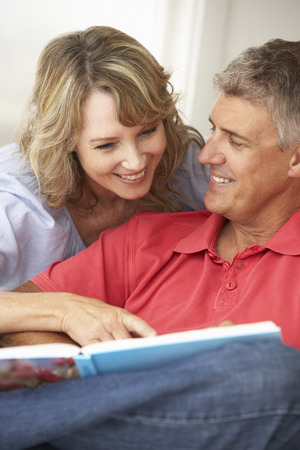 Mid age couple reading book together photo