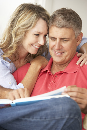 greying: Mid age couple reading book together