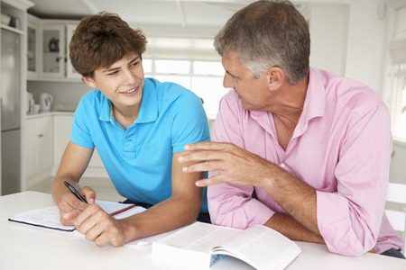 deberes: Padre ayudando a hijo adolescente con la tarea Foto de archivo