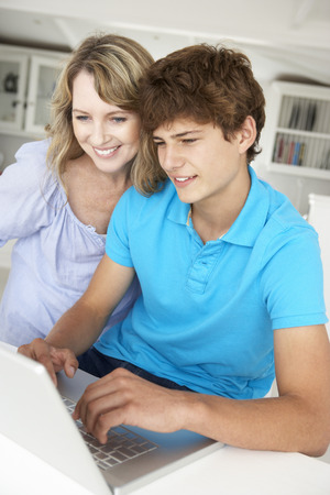 Mother and teenage son using laptop Stock Photo