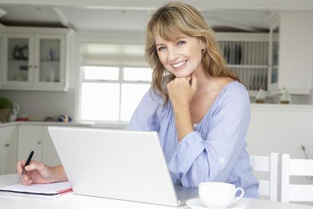 trabjando en casa: Mujer de mediana edad que trabaja en casa en la computadora portátil