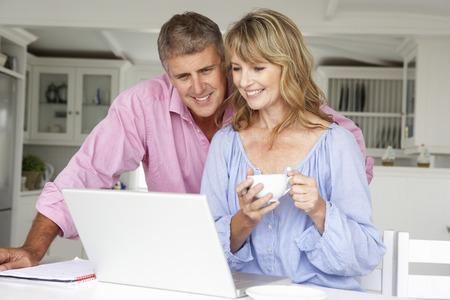 pareja en casa: Mediados de pares de la edad que trabajan en casa en la computadora portátil Foto de archivo
