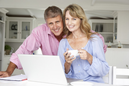 Mid age couple working at home on laptop Stock Photo