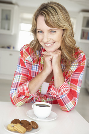 indulging: Mid age woman with coffee and biscuits at home