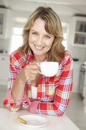 mid age: Mid age woman with coffee at home Stock Photo