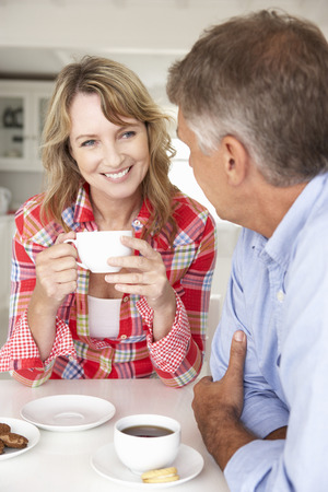 mid adult couples: Mid age couple having coffee at home