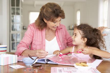 crafting: Senior woman scrapbooking with granddaughter