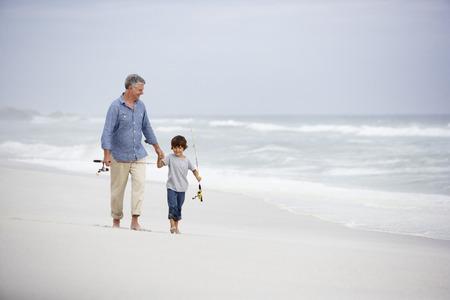 man fishing: Hombre mayor y nieto recorren en la playa Foto de archivo