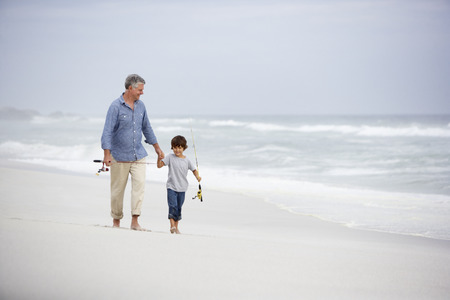 grandparent: Senior man and grandson walking on beach