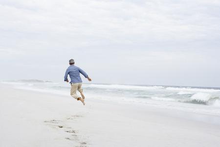 youthful: Senior man running and jumping on beach