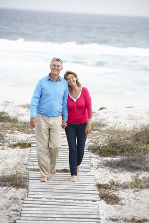 walk in: Senior couple walking by the sea Stock Photo