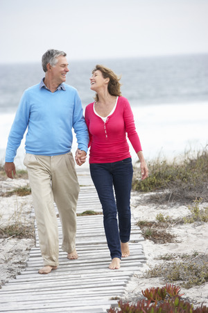 Senior couple walking by the sea Stock Photo