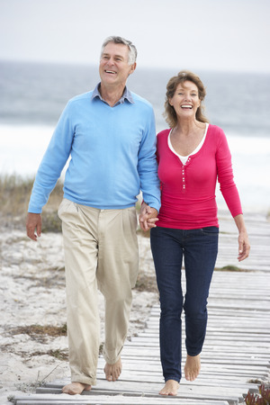 60s adult: Senior couple walking by the sea Stock Photo