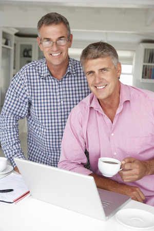 male age 40's: Mid age men working on laptop at home Stock Photo