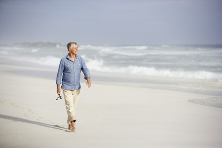 fit: Senior man walking on beach