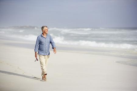 Senior man walking on beach photo
