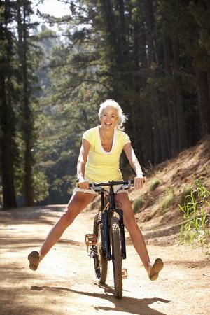 andando en bicicleta: Mujer mayor de giro libre camino rural hacia abajo Foto de archivo