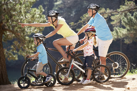 60s adult: Senior couple with grandchildren on country bike ride Stock Photo