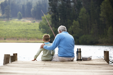 active: Senior man fishing with grandson