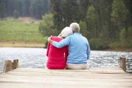hugging couple: Senior couple sitting on a jetty Stock Photo