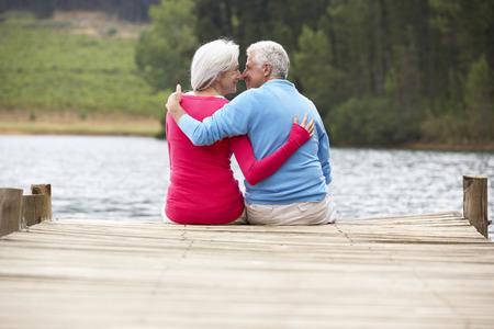 Romantic senior couple sitting on a jetty photo