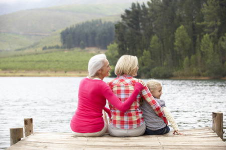 a year older: Mother, daughter and grandmother sitting on a jetty