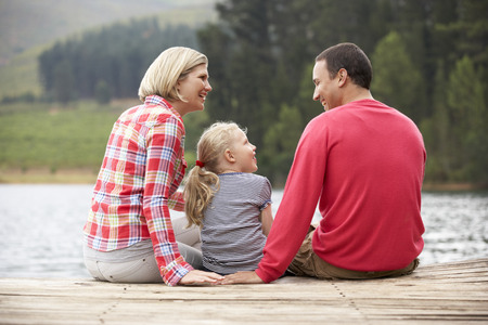 45 years old: Young family sitting on a jetty