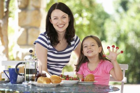 breakfast garden: Mother and daughter eating breakfast outdoors Stock Photo