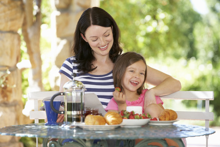 45 years old: Mother and daughter eating breakfast outdoors Stock Photo