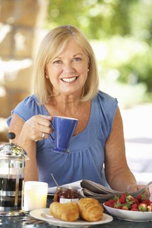 mujer tomando cafe: Desayuno mayor mujer comiendo al aire libre