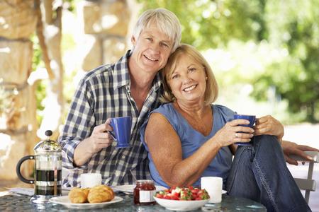 Senior couple eating breakfast outdoors Foto de archivo