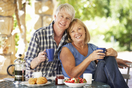 Senior couple eating breakfast outdoors Banque d'images
