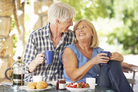 Senior paar eten ontbijt in de buitenlucht