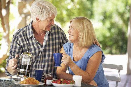 50s adult: Senior couple eating breakfast outdoors Stock Photo