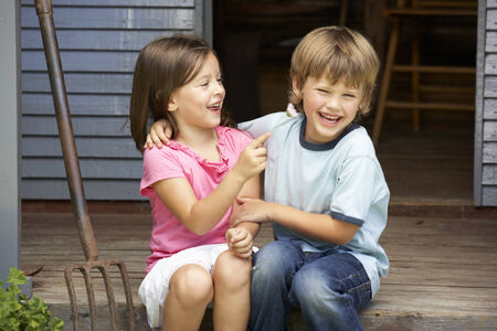 4 5 year old: Young brother and sister sitting on veranda Stock Photo