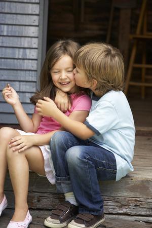 hermanos jugando: Joven muchacho hermana bes�ndose en la terraza Foto de archivo