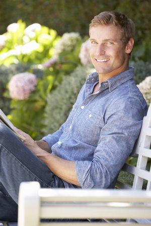 mid adult men: Man reading in garden