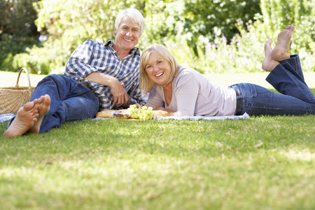 Senior couple with picnic in park Stock Photo