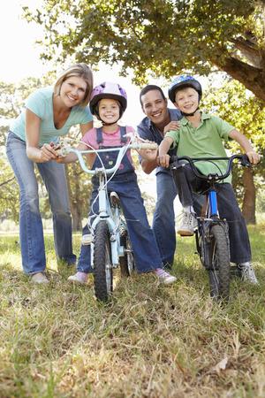 niños en bicicleta: Los padres con niños pequeños en las bicis Foto de archivo