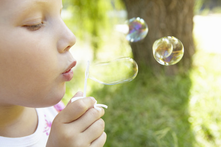 innocent girl: Little girl blowing bubbles outdoors