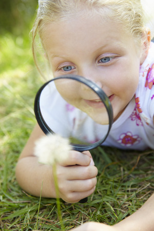 outside of the country: Little girl with magnifying glass